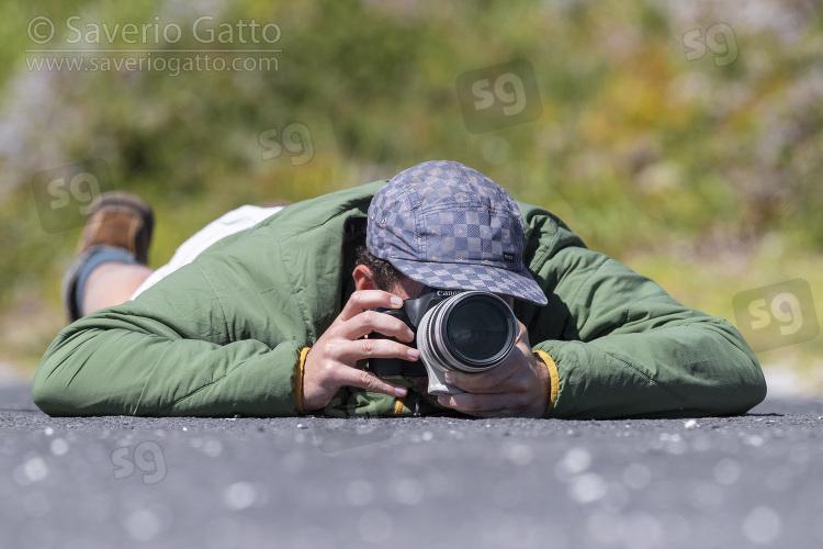 Fotografo naturalista, fotografo sdraiato in terra
